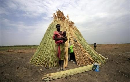 A woman from the Dinka tribe stands in front of her shelter near Bor
